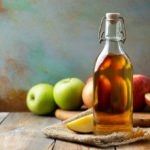 White Vinegar and apples on a raw wood table